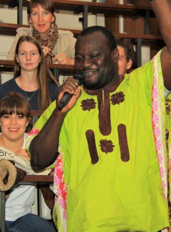 Un étudiant de Sierra Léone souriant tenant un microphone dans un amphithéâtre
